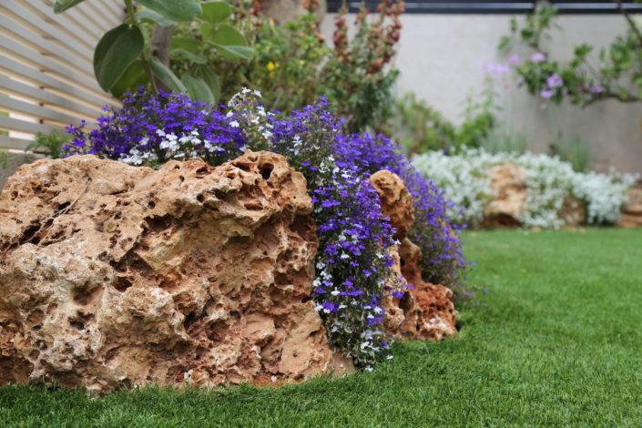 עיצוב גינה יוקרתית עם מסלעות ופרחים